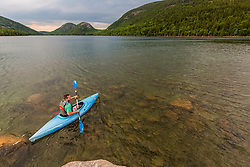 A man kayaking on Jordan Pond in Maine's Acadia National Park.