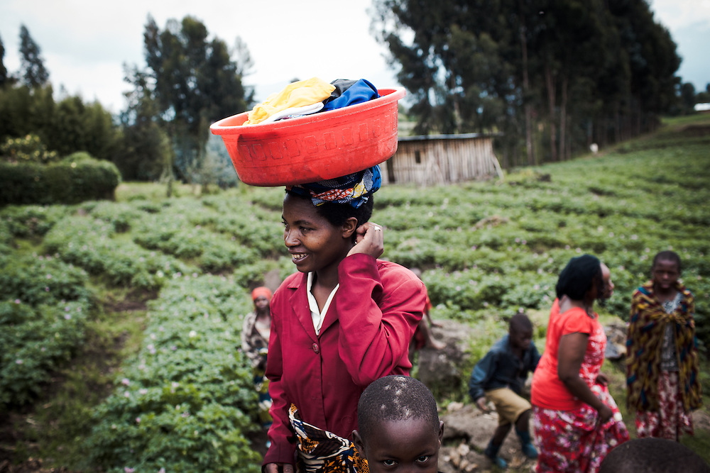 Beatrice returns to her home after doing the washing in the local river. Shingiro District, Rwanda