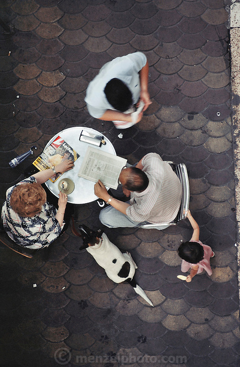 A couple with a dog and a kid reading and drinking coffee at a cafe in Valencia, Spain, shot from above.