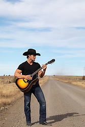 cowboy with a guitar on a dirt road