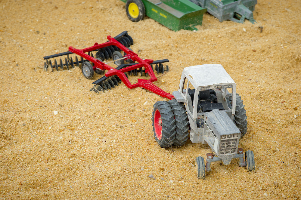 Toy tractor and disc plow in sand near  Federalsburg, Maryland, USA