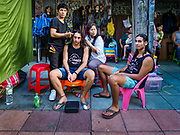 01 AUGUST 2018 - BANGKOK, THAILAND:     A tourist gets his hair braided on Khao San Road in Bangkok. Khao San Road is Bangkok's original backpacker district and is still a popular hub for travelers, with an active night market and many street food stalls. The Bangkok municipal government went through with it plans to reduce the impact of the street market on August 1 because city officials say the venders, who set up on sidewalks and public streets, pose a threat to public safety and could impede emergency vehicles. Venders are restricted to working from 6PM to midnight and fewer venders will be allowed to set up on the street. It's the latest in a series of night markets and street markets the city has closed.    PHOTO BY JACK KURTZ