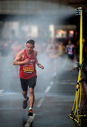 © Licensed to London News Pictures. 21/04/2013. London, UK. A competitor runs through the mist shower during the Virgin London Marathon 2013 on April 21, 2013 in London, England. Photo credit : Peter Kollanyi/LNP