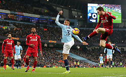 Liverpool's Andrew Robertson (right) plays the ball across the goal before Liverpool's Roberto Firmino (not in picture) scores his side's first goal of the game during the Premier League match at the Etihad Stadium, Manchester.