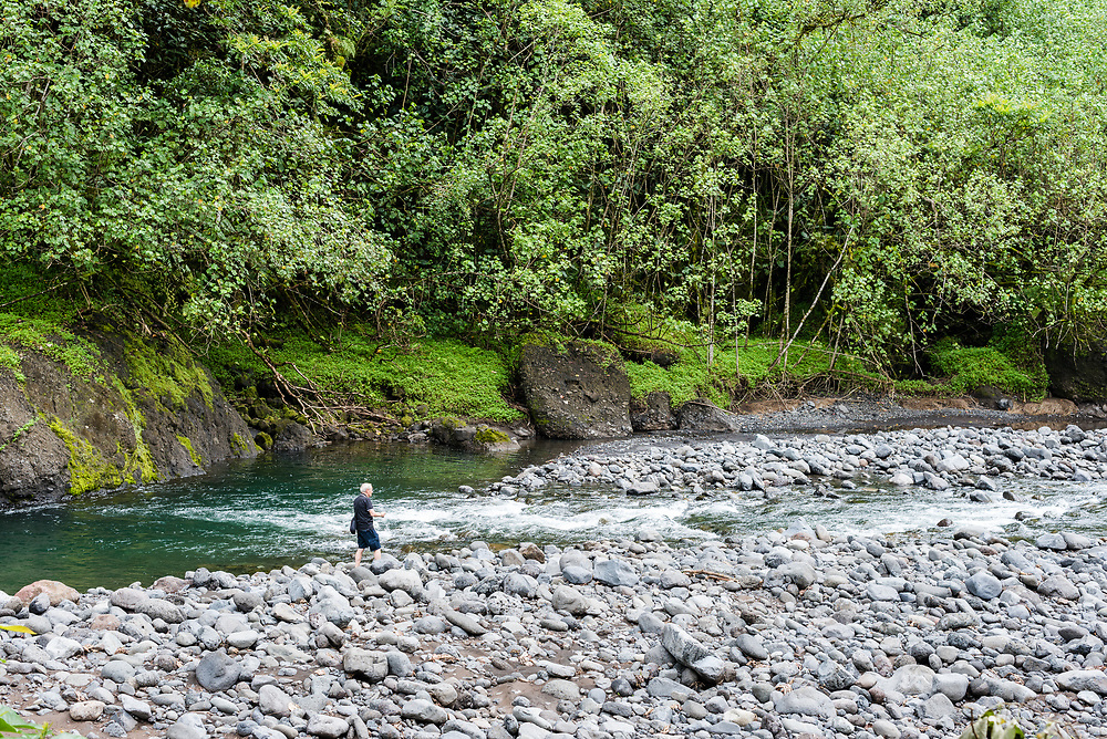 Papeete, Tahiti, French Polynesia -- March 18, 2018. A tourist walks along a rocky river bed in the Tahitian forest. Editorial Use Only.