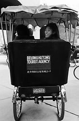 Japanese tourists on rickshaw tour of Beijing hutongs