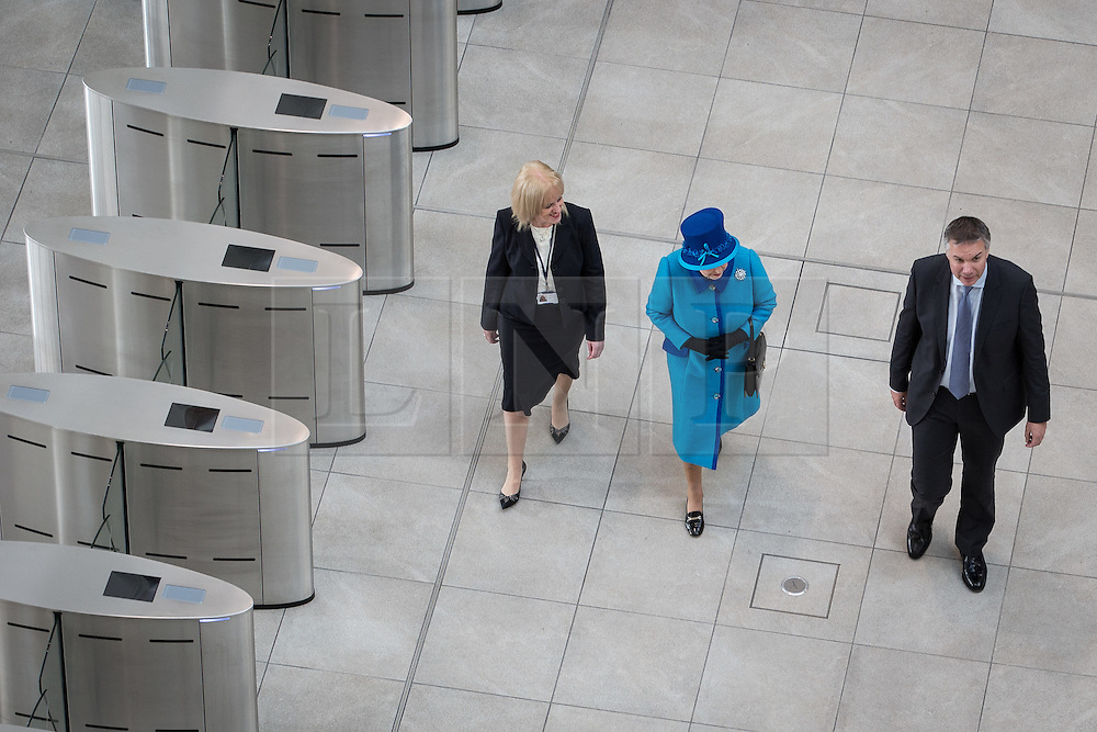 © Licensed to London News Pictures . 14/11/2013 . Manchester , UK . The Queen (in blue) crosses the foyer . Queen Elizabeth II and the Duke of Edinburgh visit the Coop building at 1 Angel Square , Manchester , this morning ( 14th November 2013 ) . Photo credit : Joel Goodman/LNP