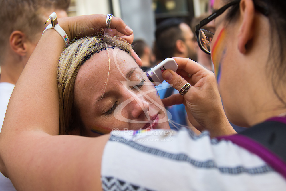 Portland Place, London, June 25th 2016. Thousands of LGBT people and their supporters gather for Pride in London, a colourful celebration of the hard-won rights of lesbian, gay, bisexual and transgender  people. PICTURED: A woman applies rainbow paint to another in Soho.