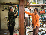 21 SEPTEMBER 2015 - BANGKOK, THAILAND: Demolition workers tear down a home near Wat Kalayanamit. Fiftyfour homes around Wat Kalayanamit, a historic Buddhist temple on the Chao Phraya River in the Thonburi section of Bangkok are being razed and the residents evicted to make way for new development at the temple. The abbot of the temple said he was evicting the residents, who have lived on the temple grounds for generations, because their homes are unsafe and because he wants to improve the temple grounds. The evictions are a part of a Bangkok trend, especially along the Chao Phraya River and BTS light rail lines. Low income people are being evicted from their long time homes to make way for urban renewal.    PHOTO BY JACK KURTZ