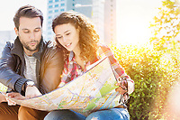 Portrait of young attractive couple sitting while looking on the map with lens flare in background