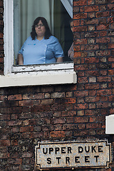 © Licensed to London News Pictures . 02/11/2015 . Liverpool , UK . A woman looks out of a first floor window at the procession for the funeral of Police Constable Dave Phillips , at Liverpool Cathedral . Five people are charged in connection with his death , including Clayton Williams , 18 , from Wallasey , who is charged with murder . Photo credit: Joel Goodman/LNP
