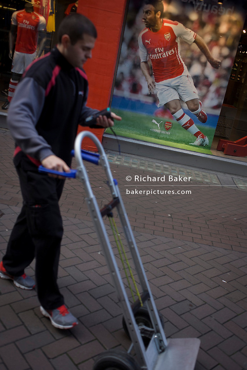 Diagonal angle of Arsenal footballer and trolley, in Carnaby Street, London.