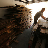 Thomas Wells | BUY at PHOTOS.DJOURNAL.COM<br /> Randy Parker continues to stack wood boards as they disassemble a home in East Tupelo that was once lived iin by Elvis Presley.
