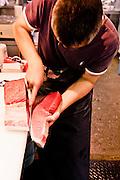 Slicing fresh tuna at Kuromon Ichiba, Osaka market