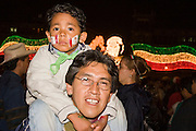 "15 SEPTEMBER 2005 - MEXICO CITY: Revelers, a father and son, on the Zocalo in Mexico City, Sept 15, for the traditional ""grito,"" the shout of ""Viva Mexico"" that marks the official start of Mexican Independence Day celebrations. Although Mexican Independence Day is Sept. 16, the celebrations usually start a couple of days before and continue through the 17th or 18th or September. It is the most important holiday on the Mexican calender. PHOTO BY JACK KURTZ"