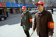 "The ""moral police"" are dispatched in Tongzhou, a suburb of Bejing. Wen Shang (R) and Tang Wendong (L) patrol their neighborhood looking for dog droppings and unauthorised advertisements. Hundreds of retired Beijing residents are queuing to join a government-approved Moral Police constabulary to rid the streets of the four ""new pests"" - spitting, swearing, smoking and queue-jumping. Wearing armbands and red caps, they are reminiscent of the 1960s Cultural Revolution and Mao's Red Guards, who roamed the countryside and ousted closet capitalists, often violently..."