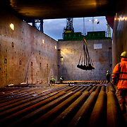 Loading steel pipe aboard a ship , Teeside, UK