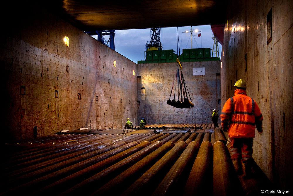 Loading steel pipe aboard a ship , Teeside, UK