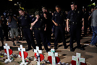 Members of the Aurora police department look over crosses for those killed in the Aurora theater shooting, at a vigil on the 5-year anniversary of the tragedy in Aurora, Colorado July 20, 2017.  REUTERS/Rick Wilking