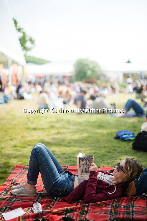 A young woman on the lawn reading her book at  the annual The Hay Festival of Literature and the Arts, 'the Woodstock of the Mind', Hay on Wye, Powys, Wales  UK May-June 2016<br /> <br /> Picture by Keith Morris/Writer Pictures