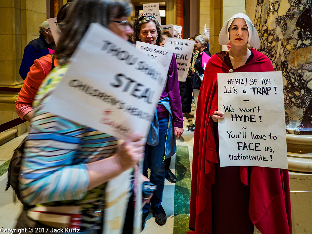 "04 MAY 2017 - ST. PAUL, MN: People protesting in favor of paid sick leave and a higher minimum wage walk past a woman dressed as a handmaid (from the novel and Hulu series ""A Handmaid's Tale"") at the Minnesota State Capitol. About 50 people came to a protest to urge Minnesota State Senators to vote against two bills supported by the Republican party that would restrict access to women's health care in Minnesota. The protest was organized by  NARAL Pro-Choice Minnesota, NCJW Minnesota, and Planned Parenthood Minnesota. The Senate passed the bills but Minnesota's Democratic governor is expected to veto the legislation when it reaches his desk.     PHOTO BY JACK KURTZ"