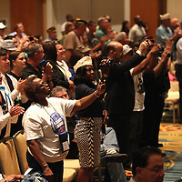 Attendees stand and take photos as President Barack Obama and First Lady Michelle Obama deliver remarks at the Disabled American Veterans  National Convention at the Orlando Hilton Ballroom in Orlando, Florida on Saturday, August 10, 2013. (AP Photo/Alex Menendez)