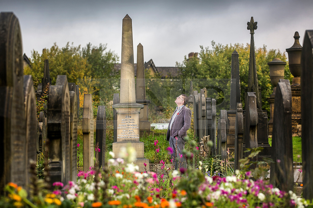 © Licensed to London News Pictures. 21/10/2015. Halifax, UK. David Glover who is the chair of the friends of Lister Lane Cemetery admires one of the Spires in The Victorian Grade 2 listed Lister Lane Cemetery in Halifax that dates back to 1841 that has been recognised as a Significant Cemetery in Europe, one of only 13 in the UK putting it alongside such famous cemeteries as Highgate in London. The cemetery houses burial plots of James Uriah Walker who was the owner of the Halifax Guardian & the first person to publish the Bronte sister's work, The Crossley family who's mill became the largest carpet manufacturing business in the world & numerous veterans of the battle of Waterloo. Photo credit: Andrew McCaren/LNP