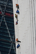 Window cleaner abseilers lower themselves down the Walkie Talkie building in the City of London.