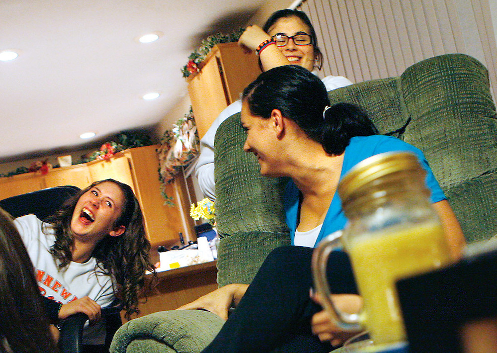 Daicee Singer, 14, left, can't help but laugh as Ashlen Ayers, 17, left, busts out her cartoonish laugh during a team dinner at Ayers' house.