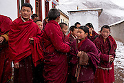 Young Buddhist monks gather in the courtyard of their mountainside monastery in Zado, Tibet (Qinghai, China).