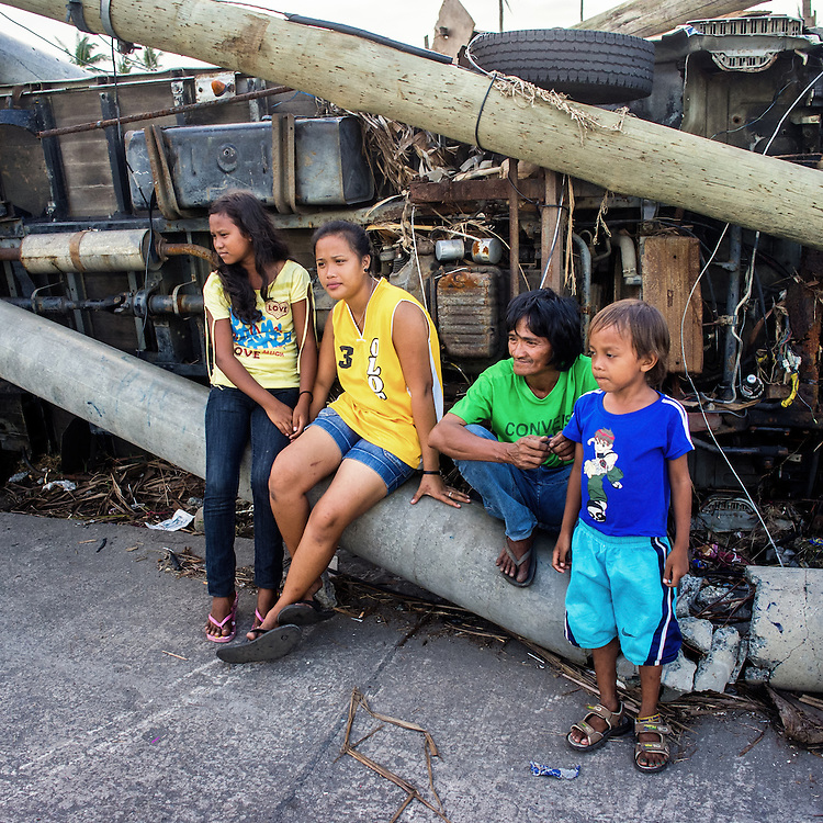 Residents sit on downed power lines and vehicle in Tanauan.