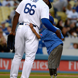 10 year-old Zion Harvey hugs Los Angeles Dodgers' Yasiel Puig after throwing out the ceremonial pitch prior to a Major League baseball game between the Arizona Diamondbacks and the Los Angeles Dodgers at Dodger Stadium on Friday, April 14, 2017 in Los Angeles. Harvey lost his legs and hands due to a sepsis infection and had complete hand replacement surgery.