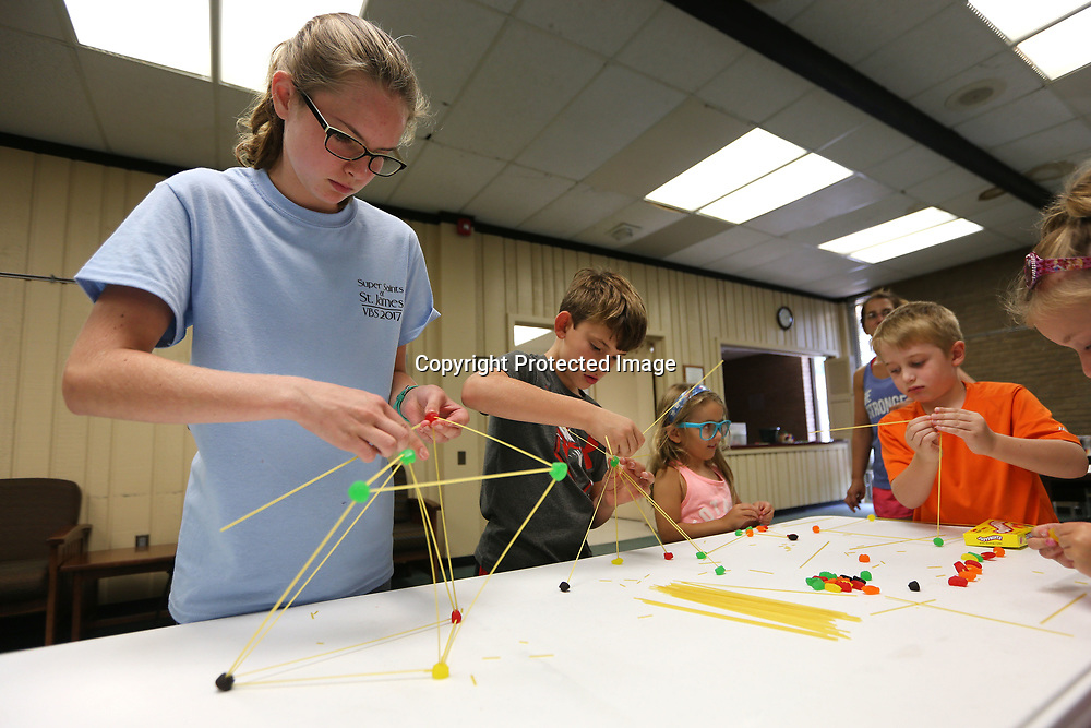 Lydia Valentine, 13, of Saltillo, puts spaghetti inside gummy candy to build a shape to stand on its own as she works with other area children on an engineering project at the Lee County Library Tuesday afternoon in Tupelo.