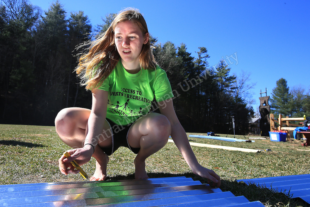 Nicole Rombach, of Davisburg, cuts metal for a roof of a garden kiosk they were helping build. She was among nine CMU students spending their Alternative Break volunteering at  theYMCA of Western NC Youth Service Center, spending the week to help with projects to improve the center and in the community. They addressed access to sports and recreation and built a kiosk, cleared a stream bed and worked with elementary students in an after school program as their Alternative Break project. CMU is ranked fourth in the nation for the number of students participating in Alternative Breaks and fifth in the country for the most trips coordinated by a university. The program organizes about 40 trips each year with more than 400 students participating. Photo by Steve Jessmore/Central Michigan University