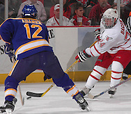 3/11/05 Omaha, Neb.University of  Nebraska at Omaha's Bill Bagron tries to move the puck past Lake Superior State's Mike Adamek Saturday night in Qwest Center Omaha. This was the first gamein the CCHA play-off.(photo by chris machianPrarie Pixel Group)