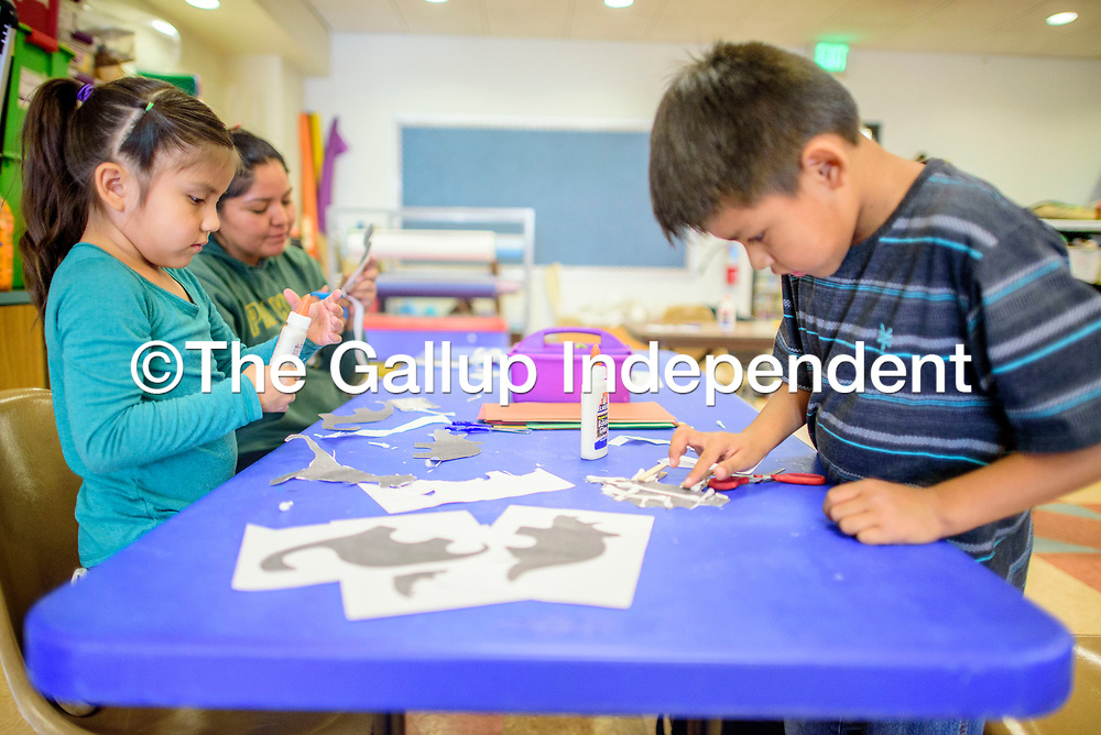 Marley Tso, 5, left, Kelly Bahe and Jacob Yazzie, 8, assemble dinosaur figures from construction paper and Q-Tips during Crafty Kids at the Octavia Fellin Public Library Children's Branch in Gallup Thursday.