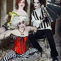 A theatrical circus featuring a male with an accordion, a female in a tophat, and a corseted female lifesize puppet