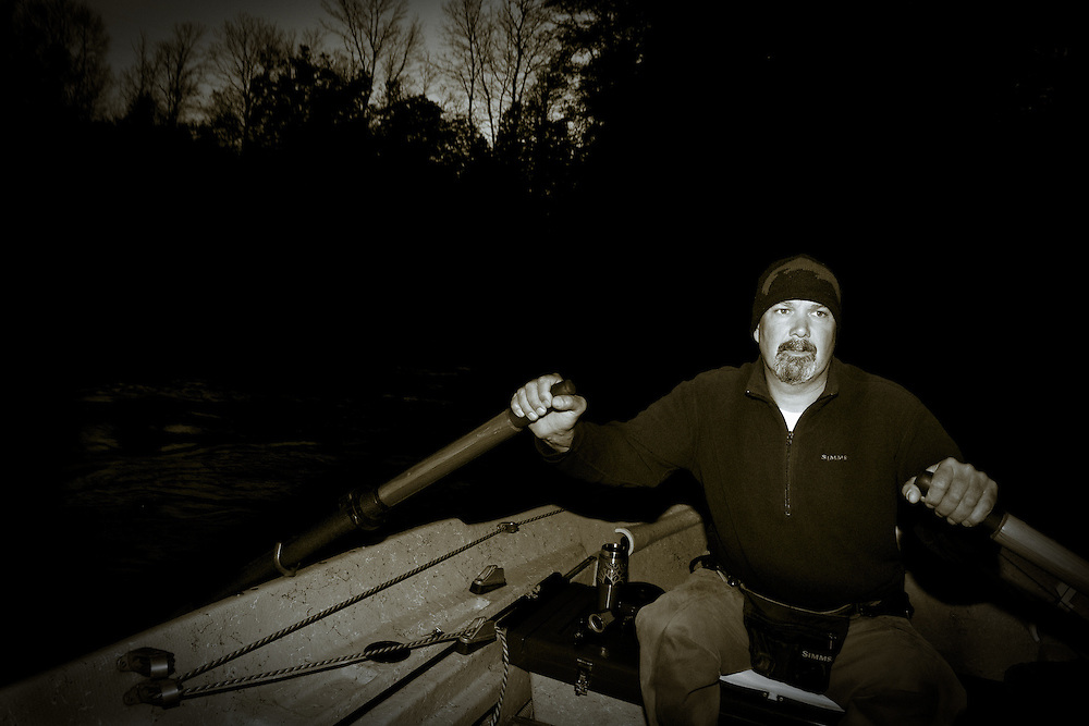 Fly fishing guide rows a drift boat on Michigan's Pere Marquette River during the fall salmon run. Early morning.