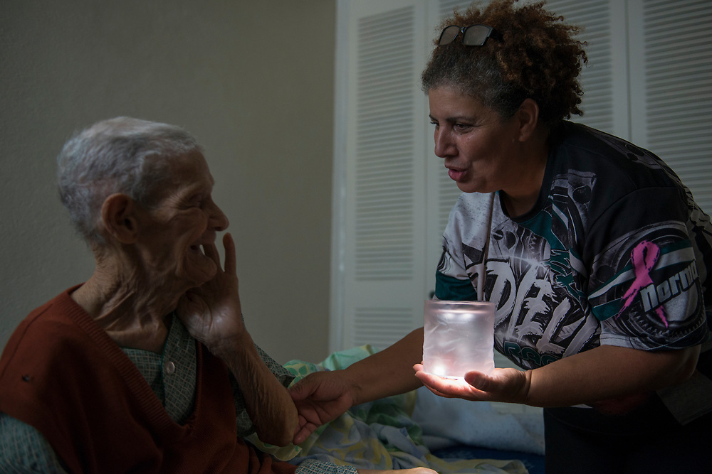 Adjuntas, PR, November 10, 2017--Rebecca Rodrigues shows Don Angelino a solar lamp during a visit to the centenarian's public housing apartment in Adjuntos, PR. Rebecca  is a volunteer at Casa Pueblo and a resident in Adjuntas, PR. Casa Pueblo is a community self-management project that is committed to the appreciation and protection of natural, cultural and human resources. It was founded in1980 to organize communities to protest proposed mining operations that would impact 36,000 acres of land in the municipalities of Adjuntas, Utuado, Lares and Jayuya. Since Hurricane Maria, Casa Pueblo has become a center for relief operations and ramped up the campaign @LightupPRcasapueblo that distributes and promotes the use of solar energy in Puerto Rico. Casa Pueblo has distributed over 6,000 solar lamps since the storm. Photo by Lori Waselchuk/braf.org