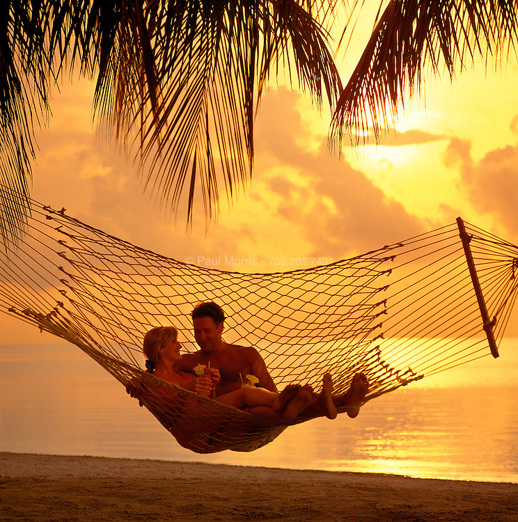 Couple lounging in a hammock between two coconut palms on the beach at sunrise.