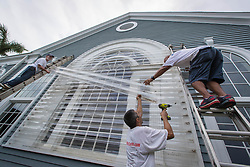 September 5, 2017 - Palm Beach, Florida, U.S. - DWAYNE LOPEZ (center) helps JEAN VIGNEAULT (left) and JOSE CINTRON (right) cover the last remaining original window at Royal Poinciana Chapel in Palm Beach. The church has replaced all the original windows with impact glass hurricane windows except this one on the north side of the sanctuary. (Credit Image: © Allen Eyestone/The Palm Beach Post via ZUMA Wire)