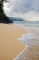 A stormy view of Hidden Beach with the Na Pali coast in the background on the North Kauai coast, Hawaii