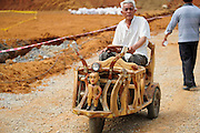 LIUZHOU, CHINA - MAY 19: (CHINA OUT) <br /> <br /> Wooden Three-wheeled Vehicle<br /> <br /> Wei Guirong and his wife pose with his home-made three-wheeled vehicles on May 19, 2014 in Liuzhou, Guangxi Province of China. Wei Guirong, 66, has made three wooden three-wheeled vehicles for grandchildren, and the vehicles are made entirely from wood, apart from the engine, wheels and some electronic parts. He was in charge of maintaining agricultural machinery when he was younger. <br /> ©Exclusivepix