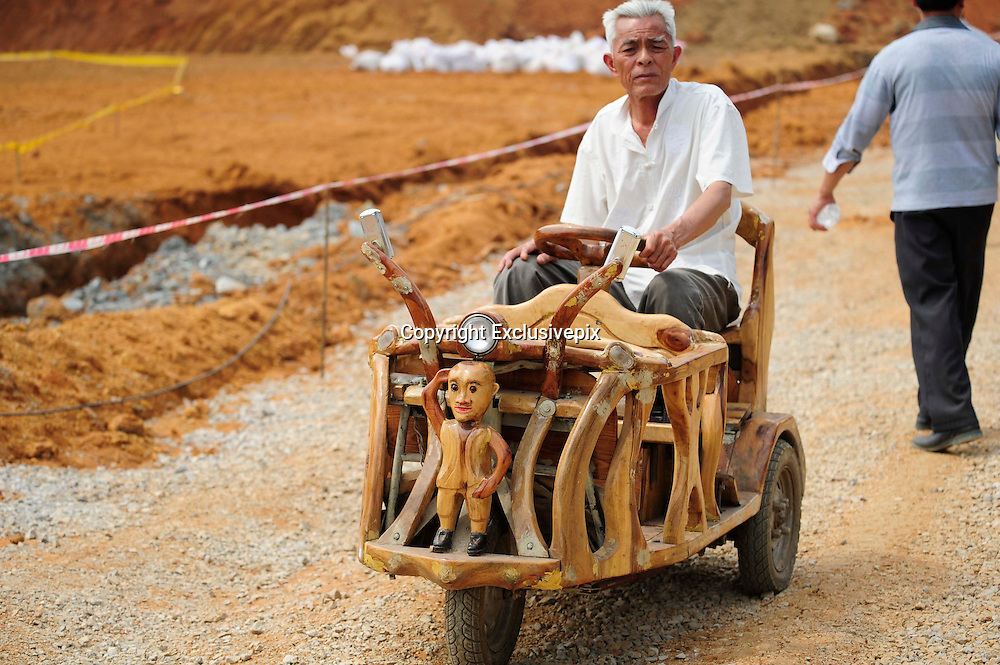 LIUZHOU, CHINA - MAY 19: (CHINA OUT) <br /> <br /> Wooden Three-wheeled Vehicle<br /> <br /> Wei Guirong and his wife pose with his home-made three-wheeled vehicles on May 19, 2014 in Liuzhou, Guangxi Province of China. Wei Guirong, 66, has made three wooden three-wheeled vehicles for grandchildren, and the vehicles are made entirely from wood, apart from the engine, wheels and some electronic parts. He was in charge of maintaining agricultural machinery when he was younger. <br /> &copy;Exclusivepix