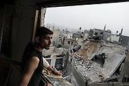 Gaza Strip, Jabaliya: A Palestinian man looks through the damaged window of his house at the destroyed by Israeli airstrike Salah Al Deen mosque (not seen) in Jabalya, a city located few kilometres north of Gaza. ALESSIO ROMENZI