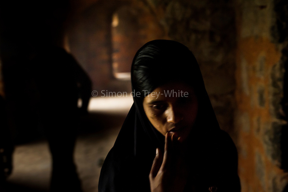 "10th December 2015, New Delhi, India. A Muslim woman in the ruins of Feroz Shah Kotla in New Delhi, India on the 10th December 2015<br /> <br /> PHOTOGRAPH BY AND COPYRIGHT OF SIMON DE TREY-WHITE a photographer in delhi<br /> + 91 98103 99809. Email: simon@simondetreywhite.com<br /> <br /> People have been coming to Firoz Shah Kotla to pray to and leave written notes and offerings for Djinns in the hopes of getting wishes granted since the late 1970's. Jinn, jann or djinn are supernatural creatures in Islamic mythology as well as pre-Islamic Arabian mythology. They are mentioned frequently in the Quran  and other Islamic texts and inhabit an unseen world called Djinnestan. In Islamic theology jinn are said to be creatures with free will, made from smokeless fire by Allah as humans were made of clay, among other things. According to the Quran, jinn have free will, and Iblīs abused this freedom in front of Allah by refusing to bow to Adam when Allah ordered angels and jinn to do so. For disobeying Allah, Iblīs was expelled from Paradise and called ""Shayṭān"" (Satan).They are usually invisible to humans, but humans do appear clearly to jinn, as they can possess them. Like humans, jinn will also be judged on the Day of Judgment and will be sent to Paradise or Hell according to their deeds. Feroz Shah Tughlaq (r. 1351–88), the Sultan of Delhi, established the fortified city of Ferozabad in 1354, as the new capital of the Delhi Sultanate, and included in it the site of the present Feroz Shah Kotla. Kotla literally means fortress or citadel."