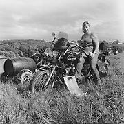 A woman sitting on a bike in the middle of a field at a Rock and Blues festival