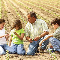 Coahoma County Cotton farmer Roge Rogers takes take out to sit and talk about the crop with his children (triplets), 2003.