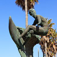 Photo of Huntington Beach surfer statue. The bronze sculpture is named Ultimate Challenge by Edmund Shumpert. Huntington Beach is a beach city located in Orange County Southern California in the United States.