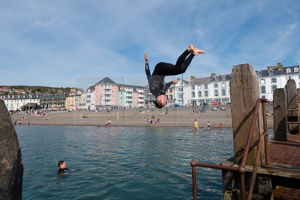 © Licenced to London News Pictures  - <br /> <br /> 23 June 2018  -  Aberystwyth Wales UK<br /> <br /> UK Weather:  Kids cool off by jumping and diving into the sea off the jetty on Aberystwyth beach  on yet another bright and sunny day, as the UK heads into a mini heatwave, with temperatures forecast to hit 29º or 30º Celsius by the middle of next week<br /> <br /> photo credit  Keith Morris / LNP